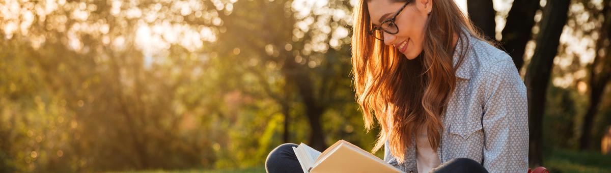 brunete su akiniais sedi ant suoliuko ir skaito knyga parke