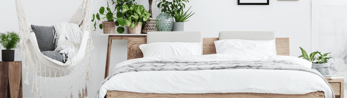 didelis ir erdvus sviesus miegamasis su baltomis pagalvemis ant lovos